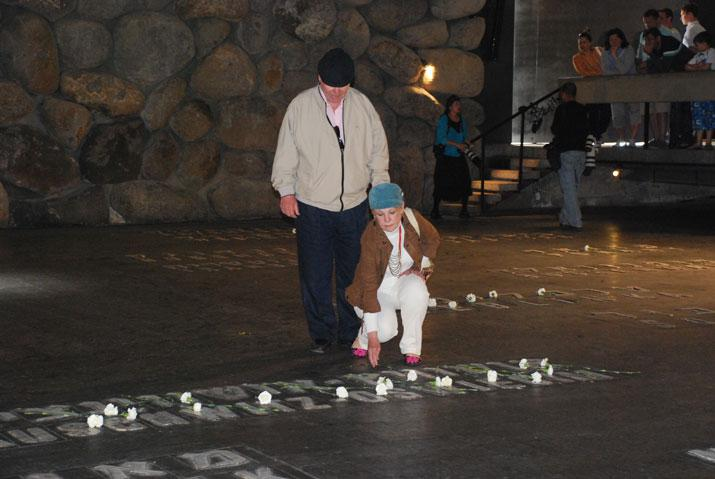 Visitors to Yad Vashem place a flower in the Hall of Remembrance after reciting the names of loved ones