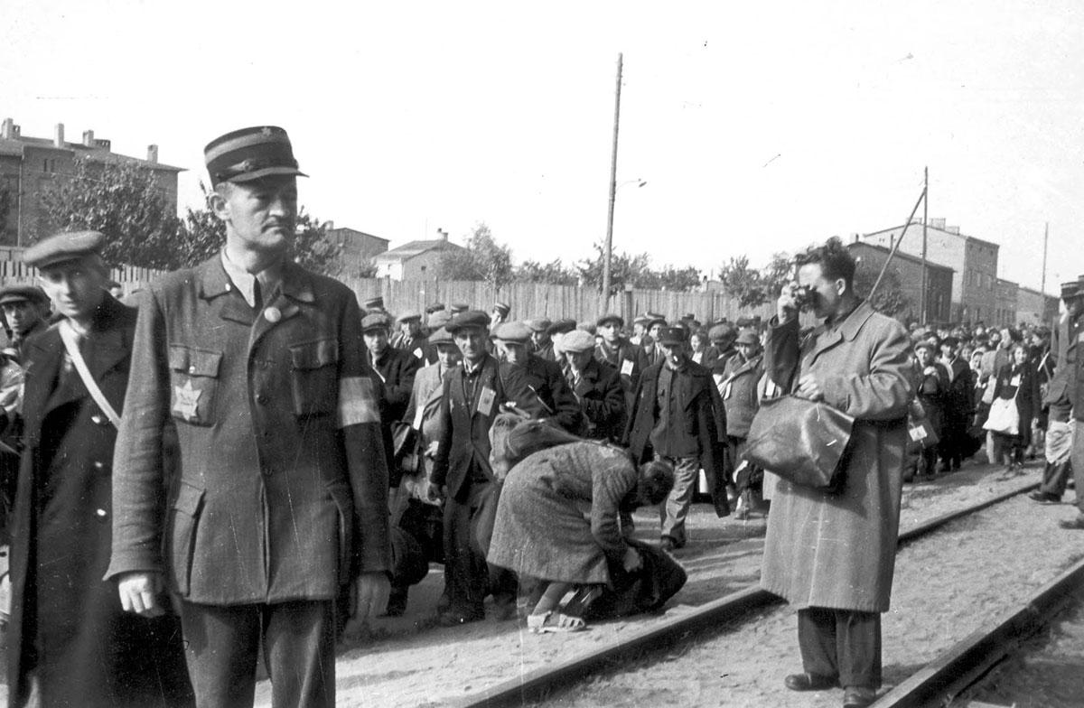 Mendel Grossman photographing a deportation of Jews from the Lodz ghetto. The photo was taken by Grossman's assistant, Arieh Ben Menachem