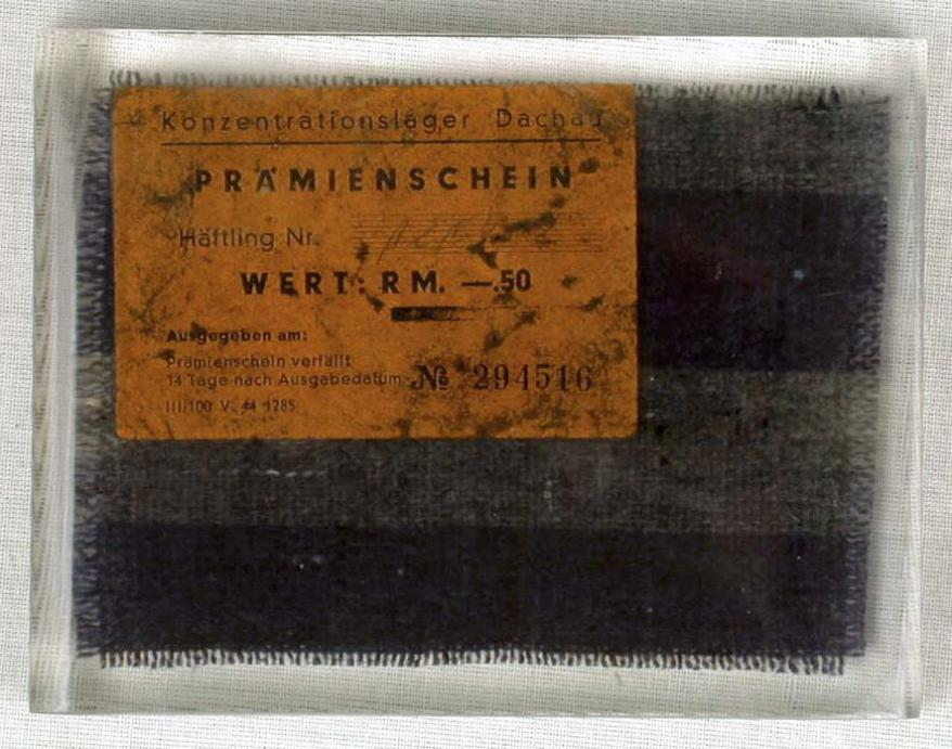 Remnant of prisoner clothing and a cigarette coupon that Leo Goldner took when he was liberated from the Allach-Dachau concentration camp