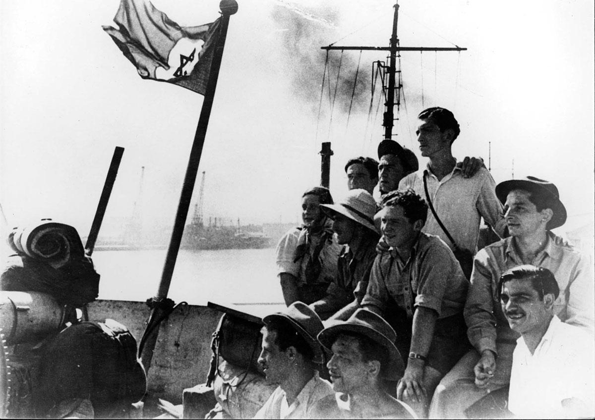 "Illegal immigrants on the deck of the ""Pan York"" on the day they arrived in Israel, 14 August 1948. Center, far right (with the hat) Holocaust survivor Yaacov (Jacki) Handeli"