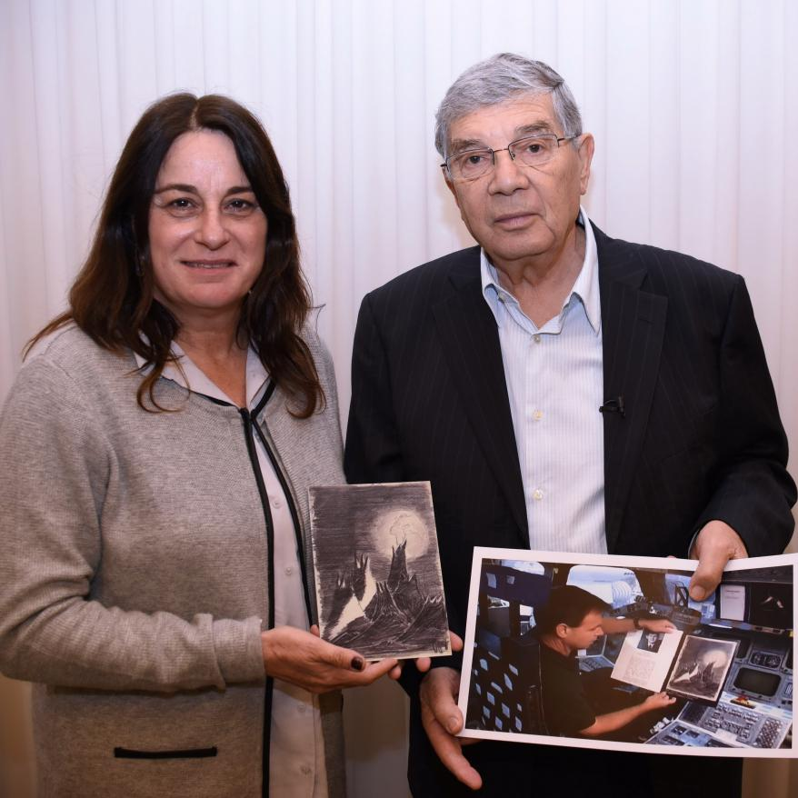 """Avner Shalev and Rona Ramon with a copy of Petr Ginz's """"Moon Landscape."""" and a photograph of Ilan Ramon before his doomed space mission"""