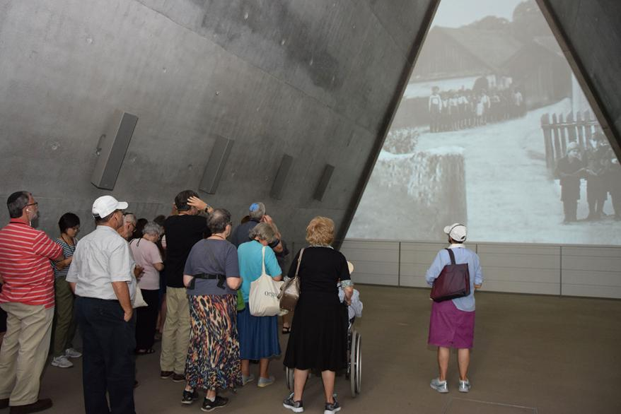 """The group begins their tour of the museum by looking at """"I Still See Their Eyes: The Vanished Jewish World,"""" a video art exhibition by Michal Rovner"""