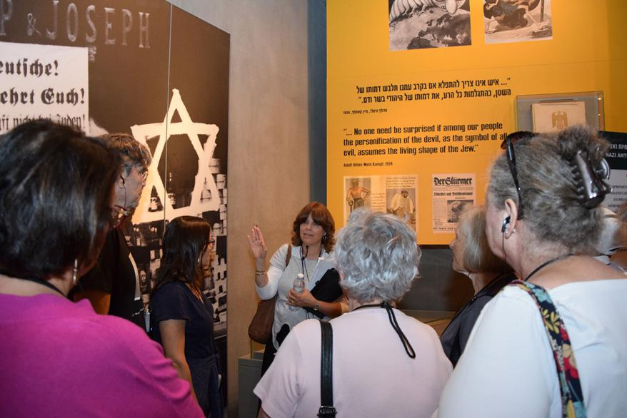 Debby Spero explaining an exhibit during the tour in the Holocaust History Museum