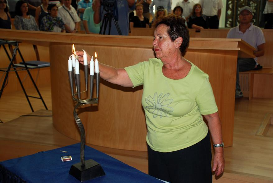 A Holocaust survivor from Greece lighting a candelabra to commemorate the Jews of Rhodes and Kos who were murdered in the Shoah, the Synagogue, Yad Vashem