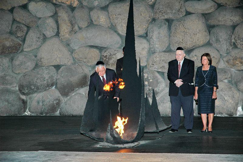President Kaczynski rekindles the Eternal Flame at the memorial ceremony in the Hall of Remembrance.  Standing behind him are his wife and the Chairman of the Yad Vashem Council Joseph (Tommy) Lapid