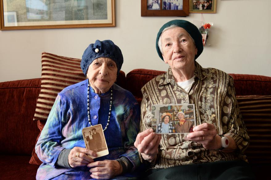 Miriam and Sarah Goldstein holding photographs of themselves dress in costume for Purim