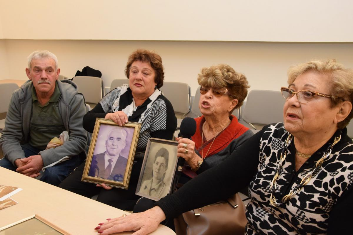 Left to right: Gennadi Band, Fania Band Blakay,  Henia Borenstein Moskowitz and Rywka Borenstein Patchnik  holding pictures of siblings Nisan Band and Jenta Band Borenstein