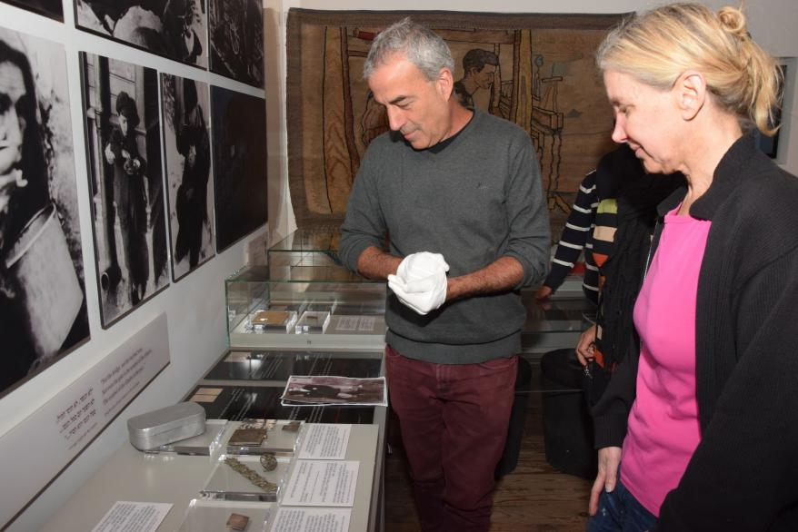 Yad Vashem's Artifacts Department Director Michael Tal shows Tina Rosenstein her grandfather's powder compact as it is displayed in the Holocaust History Museum
