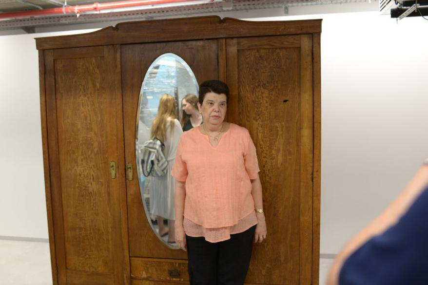 Tamar Doron, daughter of Genia Bartov (nee Sznajder), standing in front of the armoire that saved her mother's life during the Holocaust at Yad Vashem