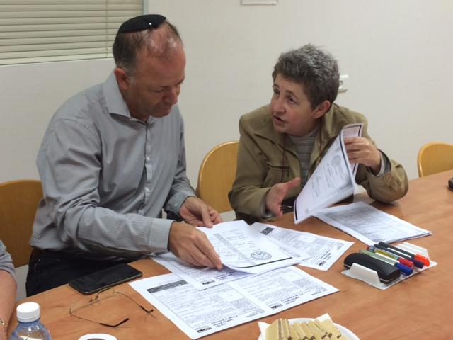 Dr. Haim Gertner and Rita Margolin reading archival documents with information about the siblings