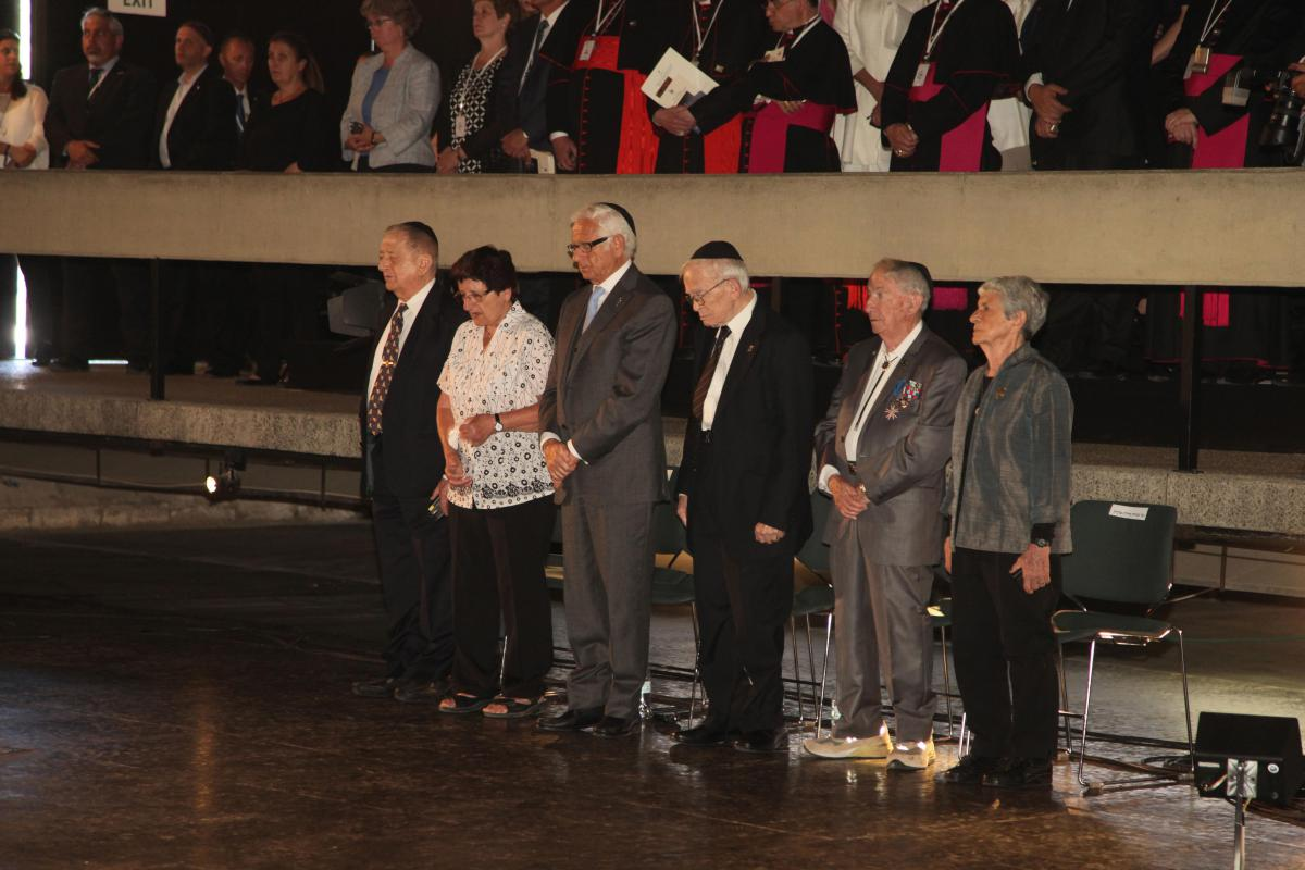 Six Holocaust survivors representing the six million Jews murdered in the Holocaust