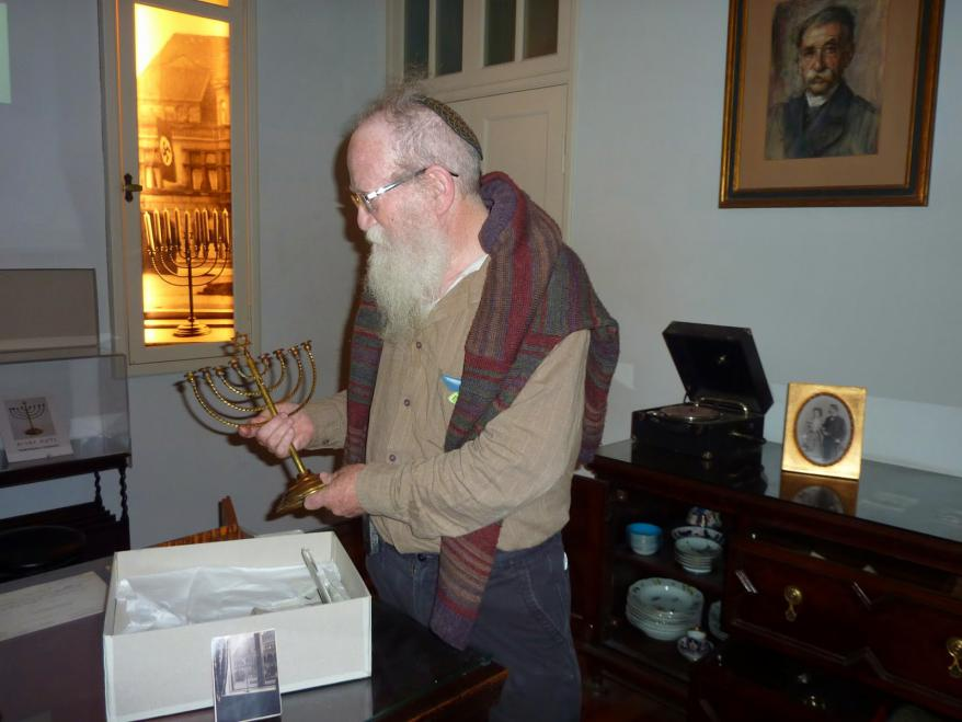 Yehudah Mansbach carefully packing up his grandfather's Hanukkah  menorah which is on display at Yad Vashem throughout the year,  except during the festival of Hanukkah.