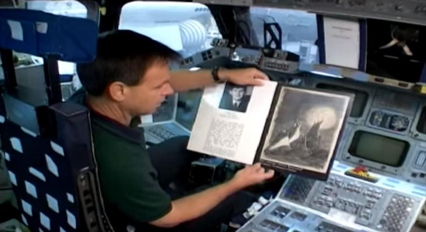"""Ilan Ramon z""""l photographed with Petr Ginz's drawing prior to Ramon's space mission"""