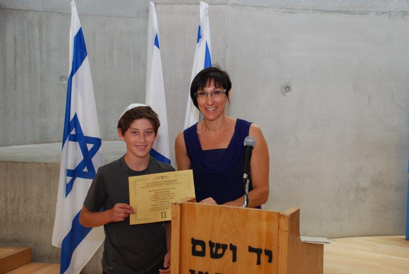 """Cynthia Wroclawski , Manager of the Shoah Victims' Names Recovery  Project grants Jalen Schlosberg the """"twinning"""" certificate honoring the  memory of his 3rd cousin Haim Okham who was murdered in the Holocaust"""