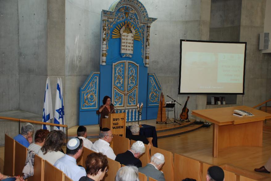 Maggie Cohen detailing a book designed to commemorate the Jewish communities of Rhodes and Kos in the synagogue at Yad Vashem
