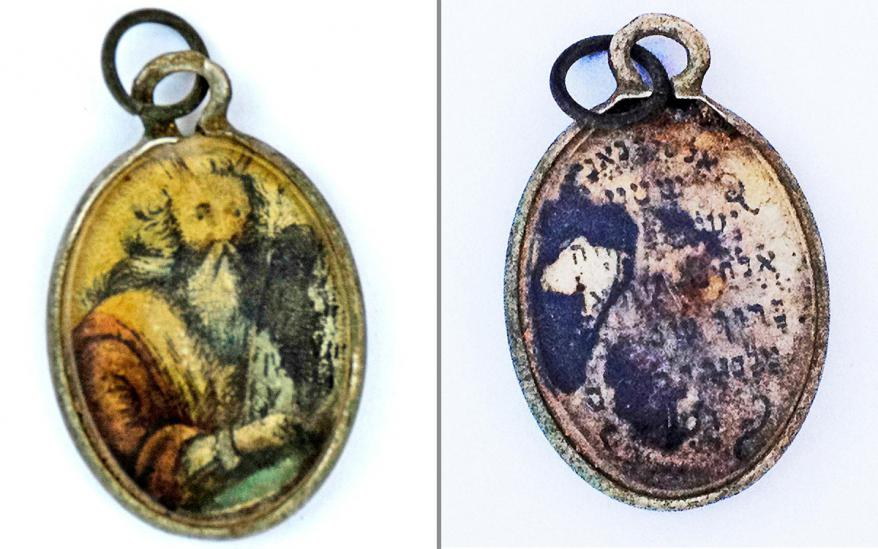 """A metal charm covered with glass with the image of  Moses holding the Ten Commandments painted on it.  Engraved on the reverse side is the c entral Jewish prayer  """"Shema"""""""