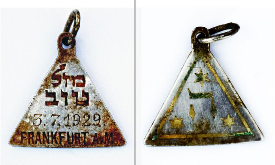 """The front and the reverse side of the pendant bears the words writing """"Mazal Tov,"""" the Hebrew letter  """"He"""" and three Stars of  David"""