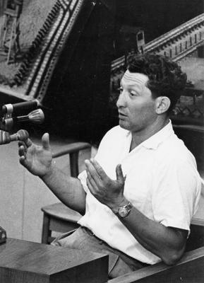 Shimon Srebernik giving testimony at the Eichmann trial, demonstrating the length of his leg irons with his hands, 1961