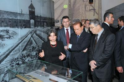 Italian Prime Minister Silvio Berlusconi studies the Auschwitz Album in the Holocaust History Museum. From the right: Chairman of the Yad Vashem Directorate Avner Shalev, Berlusconi, Education Minister Gideon Sa'ar, and Dr. Iael Nidam-Orvieto