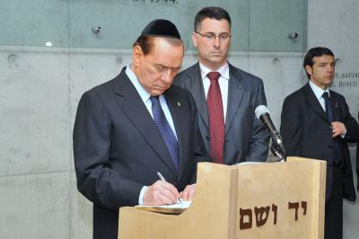 Italian Prime Minister Silvio Berlusconi signs the Visitors' Book upon exiting the Children's Memorial