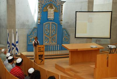 Cheryl Finkelstein (Priven) speaks about the family discovery during Jalen Schlosberg's twinning Bar Mitzvah ceremony at the Synagogue in Yad Vashem Jerusalem
