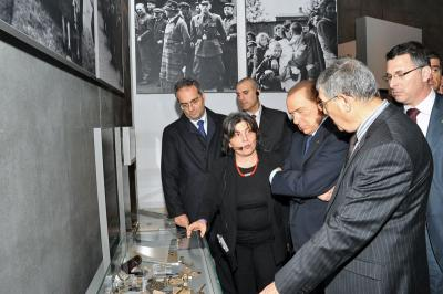 Prime Minister Berlusconi studies an exhibit in the Holocaust History Museum of objects taken from Italian Jews before their deportation to Auschwitz