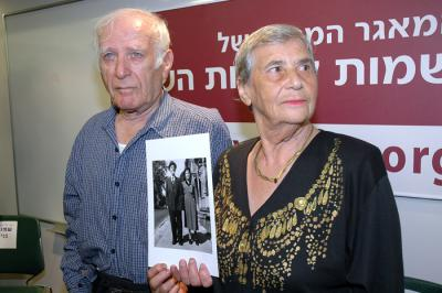 Hilda Shlick and Simon Glasberg holding a photo of their parents