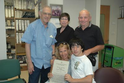 Naomi and Morris Shlomovitz with their grandson Matthew Glaser holding a memorial certificate for Zisha Katz pictured with newly found family members Gerald and Jan Schor