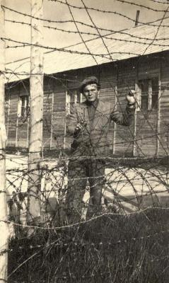 A survivor stands behind barbed wire at the Displaced Persons camp in Bari, Italy, 1947
