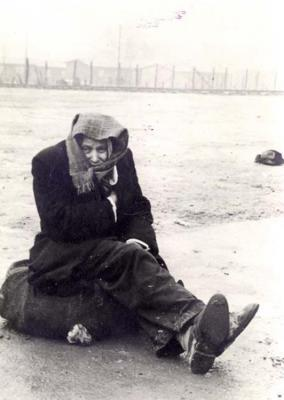 A survivor sits on a bundle of possessions after liberation, Dachau, Germany