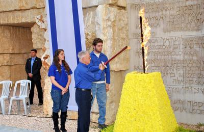Holocaust survivor Ehud Loeb, born in Buehl, Germany, lights the torch during the ceremony