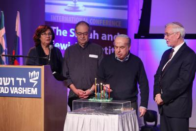 Jewish Agency Chairman Natan Sharansky lights a menorah created at a DP camp after the war