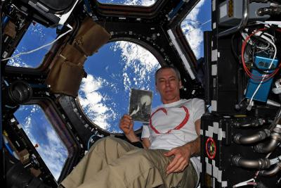 "Drew Feustel holding a replica of ""Moon Landscape"" while orbiting the Earth"