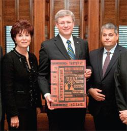 Fran Sonshine, National Chair (left), and Yaron Ashkenazi, Executive Director of the Canadian Society for Yad Vashem (right) present the Carol Deutsch Portfolio to the Rt. Hon. Stephen Harper, Prime Minister of Canada