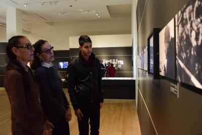 Twins Iudit Barnea and Lia Huber look at photos of the Soviet liberation of Auschwitz, at which they were present