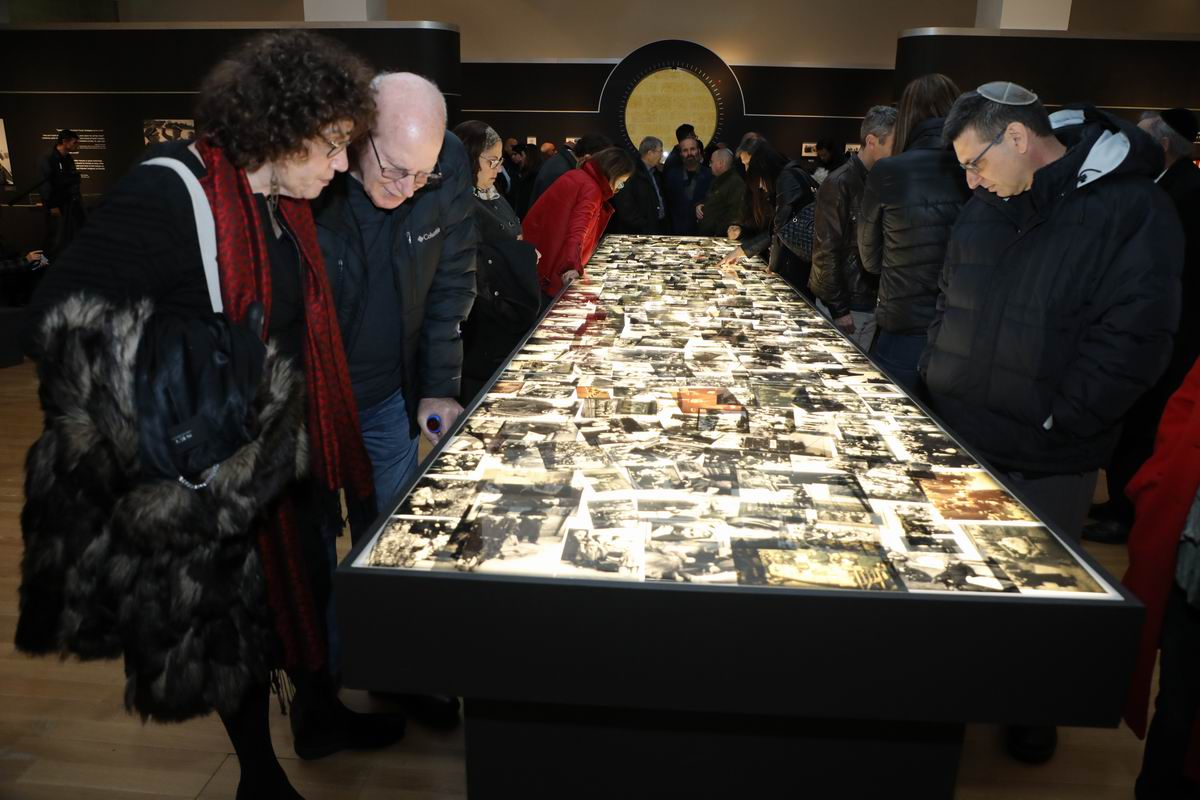 A light table down the center of the exhibition displays over 1500 photographs taken during World War II