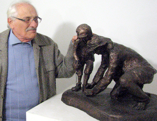 Willenberg and his sculpture of the father helping his son take off his shoes