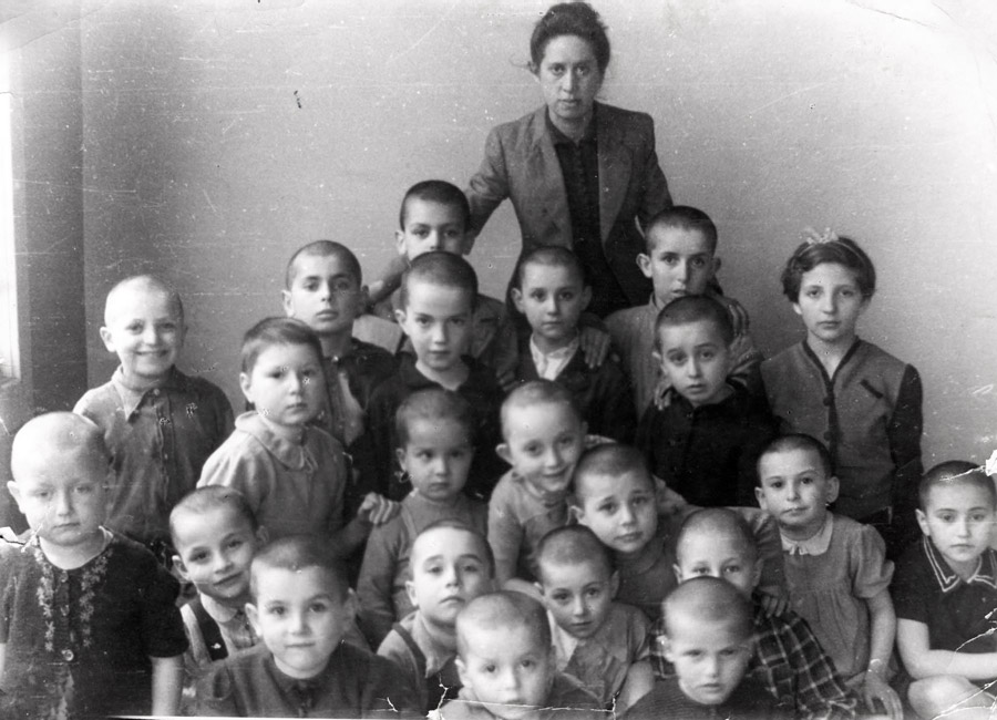 Children in the home shortly after their arrival along with the teacher Franciszka Oliwa. The children's heads were shaved upon arrival in order to rid them of lice