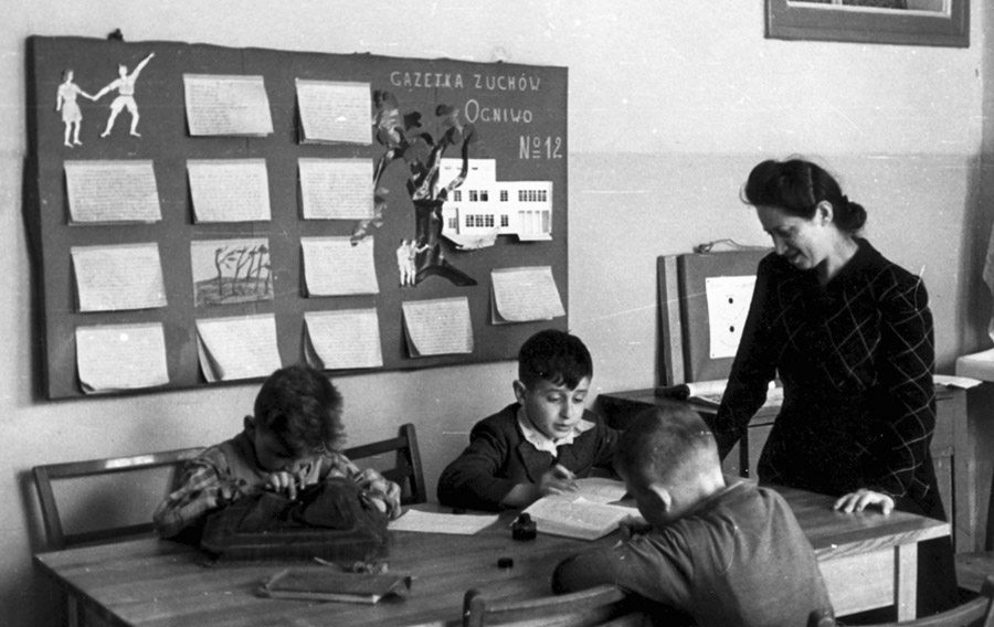"Students and the teacher Franciszka Oliwa in a classroom. In the background on the wall is a children's newspaper published by the children in the home. The paper's name is ""The Young Scout's Newspaper (Gazetka Zuchow Ogniwo), Group #12"""