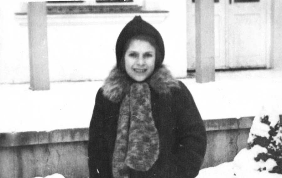 Hanka Federman, born in 1936, standing in the snow and holding her school bag