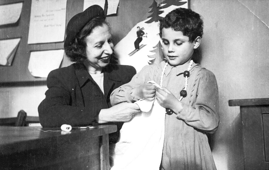 A child and teacher in the home during a sewing lesson