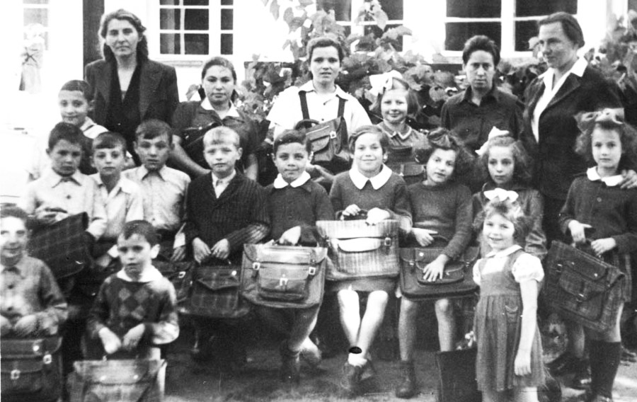 A group of children in the home all holding their school bags. In the top row on the right is Luba Bielicka Blum, the director of the home, and next to her is Franciszka Oliwa, the teacher for the middle group