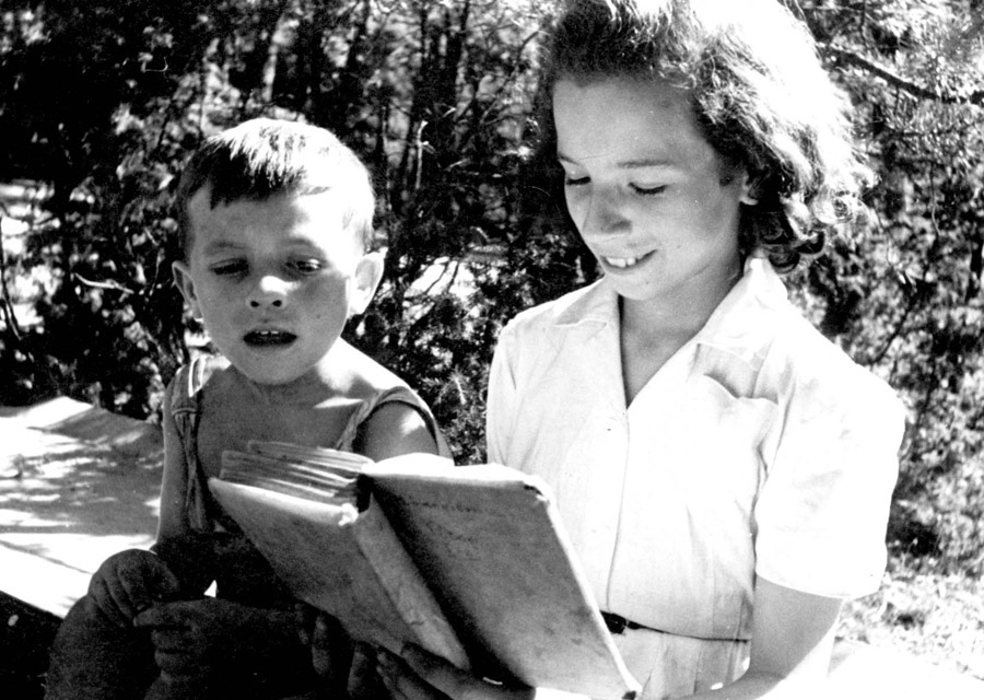 An older girl reads to a younger child in the home