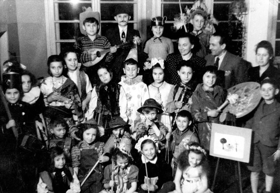 A Purim celebration in the home. In the first row, with the white hat, is Petronela