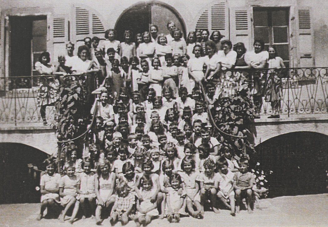 Photograph of all the children and staff (on the upper rows), at the children's home, on the same steps as the previous photo. Pringy, 1943